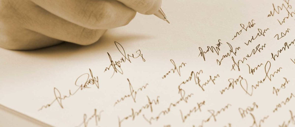 Image of man's hand holding a pen over a page of handwritten text.